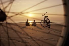 Amanecer de sol. playa a través de los radios de una bici